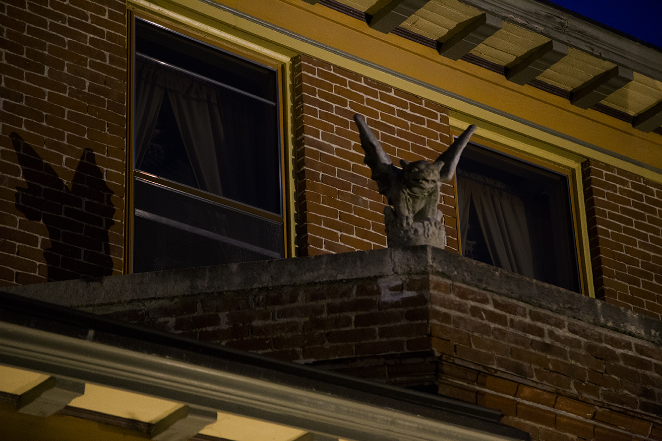 gargoyle on top of balcony ledge with light