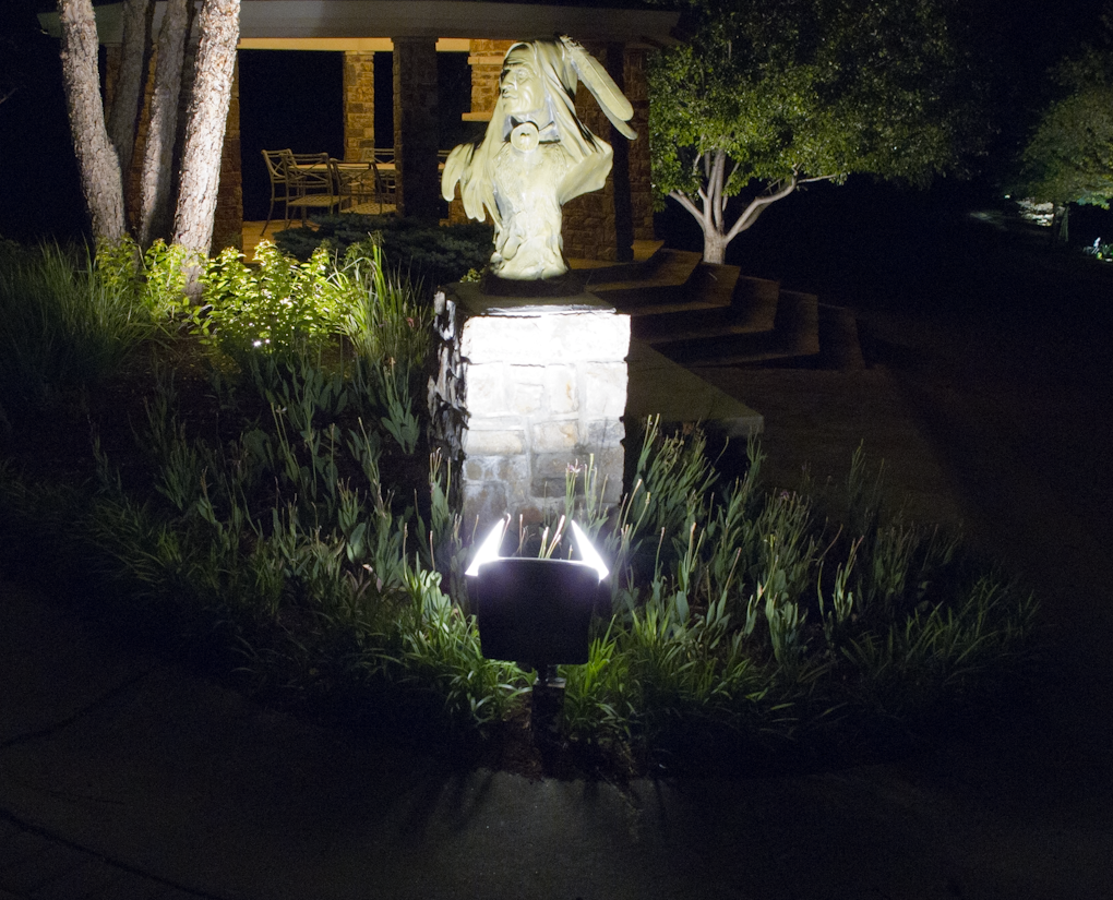 a Native American head statue with light in garden